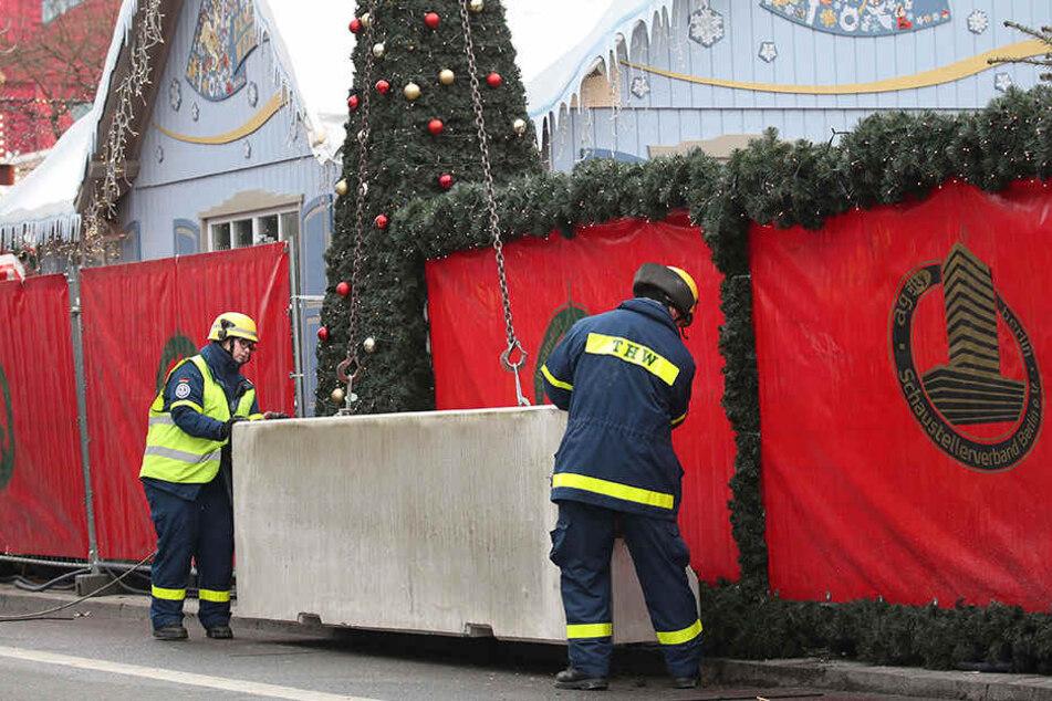 Feuerwehrmänner platzieren den Betonpoller vor dem Weihnachtsmarkt am Breitscheidplatz.