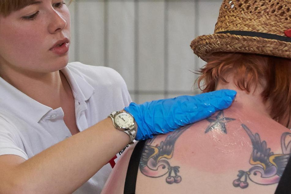 Eine Sanitäterin versorgt einen schweren Sonnenbrand. (Symbolbild)