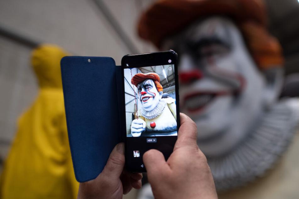 """Ein Besucher fotografiert den Karnevalswagen mit dem amerikanischen Präsidenten Donald Trump als Horrorclown """"Penny Wise"""" aus dem Film """"Es""""."""