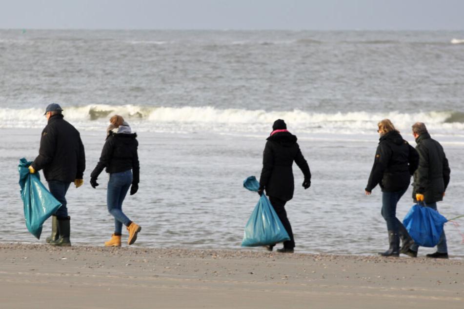 Helfer suchen am Strand von Borkum nach angeschwemmten Treibgut.