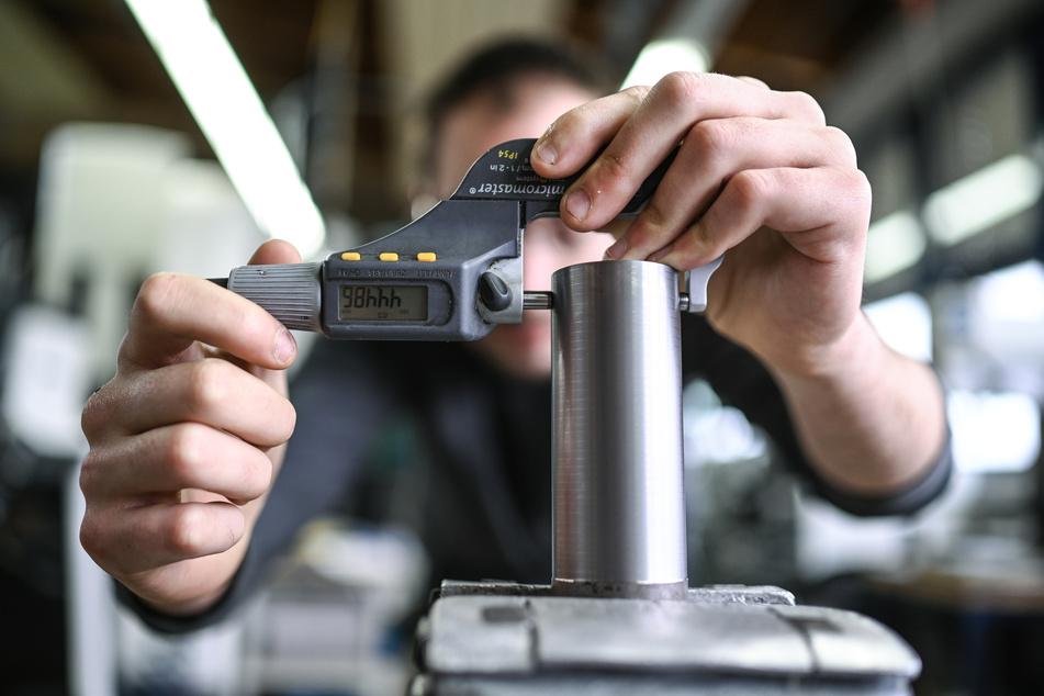 Ein Auszubildender im Metall-Handwerk misst in einem Ausbildungszentrum die Dicke eines Werkstücks.