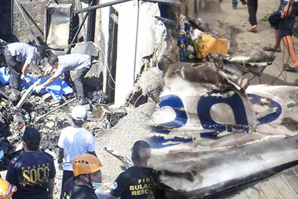 Die Helfer stehen in den Trümmerteilen.
