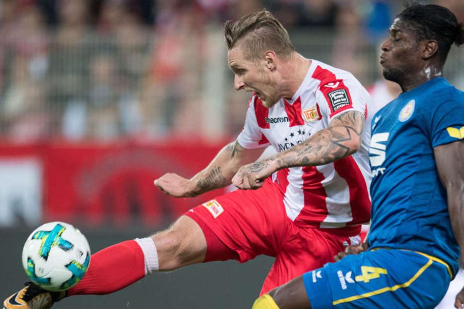 Unions Sebastian Polter schießt den Ball gegen Braunschweigs Joseph Baffo (r).