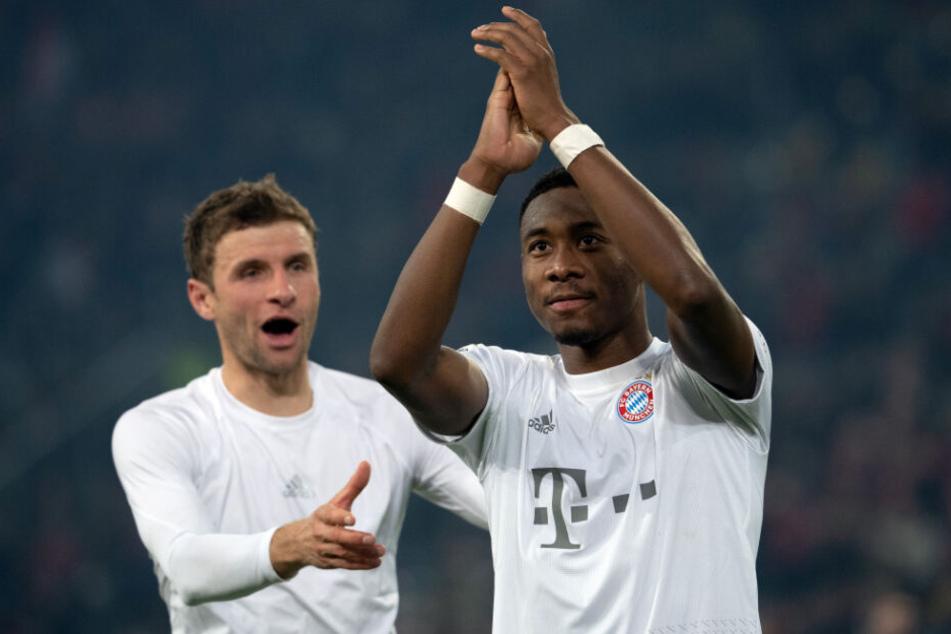 Thomas Müller (l) und David Alaba feiern nach einem Sieg des FC Bayern.