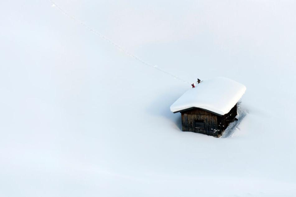 Ein Haus in Österreich in den Schneemassen: Menschen räumen das Dach frei.