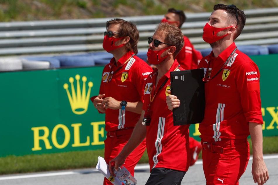 Sebastian Vettel (M) aus Deutschland vom Team Ferrari inspiziert mit seinem Team die Strecke.