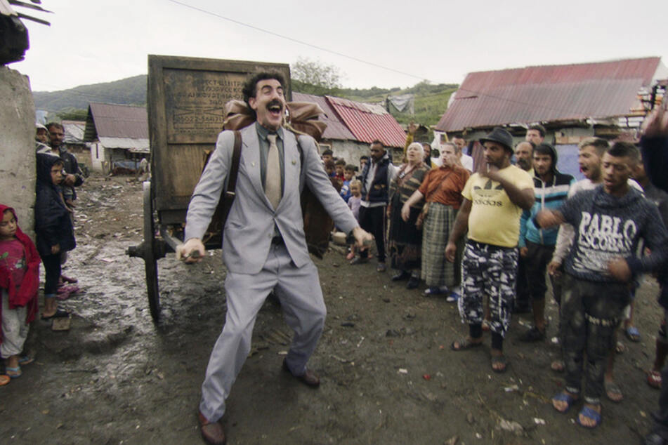 Frohen Mutes bricht Borat Sagdiyev (Sacha Baron Cohen) mit Johnny, dem Affen (in der Kiste), aus seinem kasachischen Dorf in die USA auf.