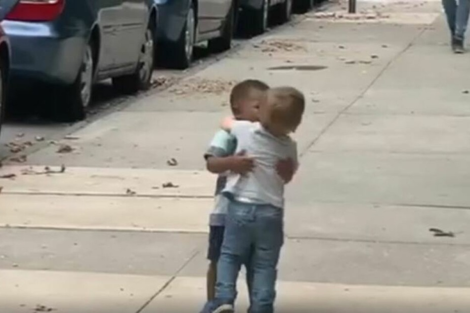 Die beiden Jungs liegen sich in den Armen.