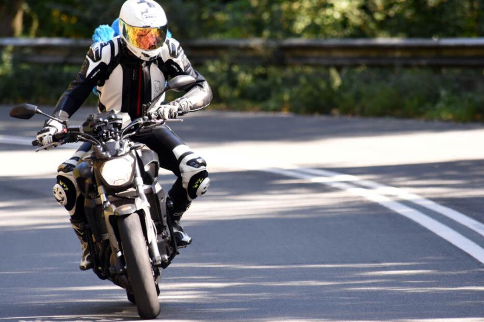 Ein Motorradfahrer fährt auf einer Straße. (Symbolbild)