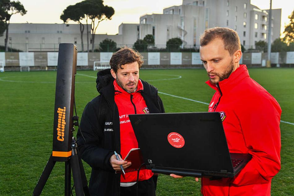 Fitnesscoach Philippe Hasler (l.) und Sportwissenschaftler Jacob Wolf überwachen die eingehenden Daten der einzelnen Dynamo-Spieler, beginnen noch auf dem Platz mit der Auswertung.