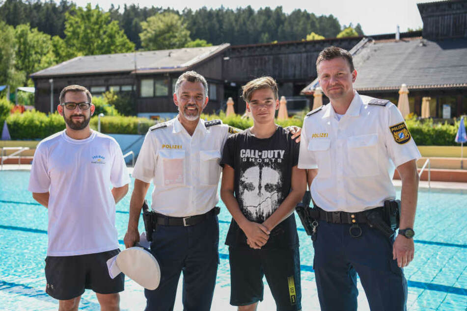Der 13-Jährige Justin Fischer (2.v.r.) steht zusammen mit Bademeister Benjamin Höllerer (l) und den beiden Polizisten Michael Mutzbauer (2.v.l.) und Alexander Horn (r) vor dem Nichtschwimmerbecken im Freibad.