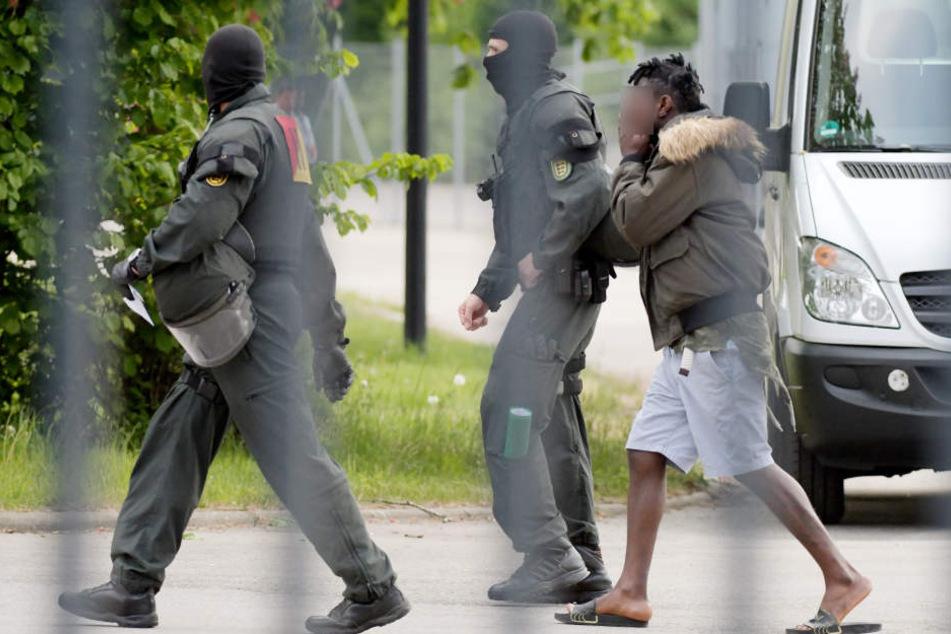 In der Landeserstaufnahmeeinrichtung für Flüchtlinge (LEA) wird ein gefesselter Mann von maskierten Polizisten abgeführt. (Archivbild)
