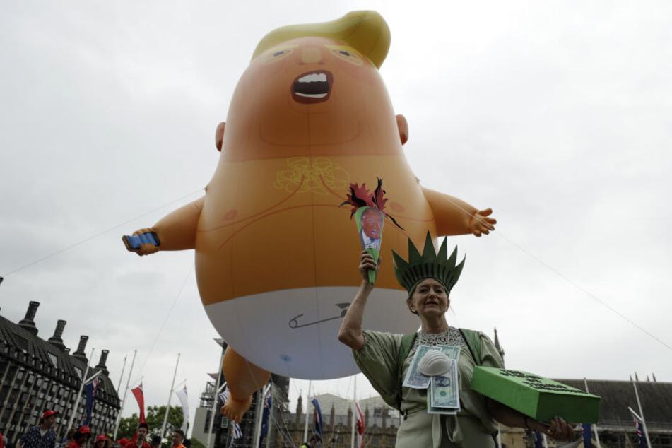 """Über den Köpfen der Anti-Trump-Protestler erhebt sich """"Baby Trump Ballon""""."""