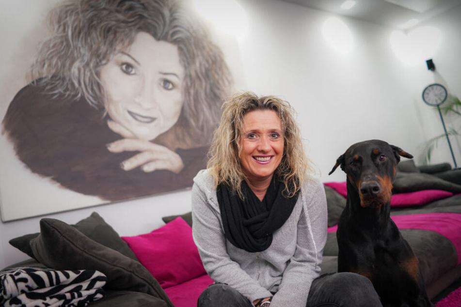 Daniela Alfinito zusammen mit ihrem Dobermann Falcon im heimischen Wohnzimmer.