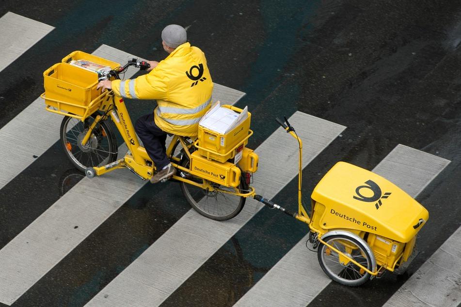 Ein Briefträger der Deutschen Post fährt mit einem Fahrrad (E-Bike) über einen Zebrastreifen.