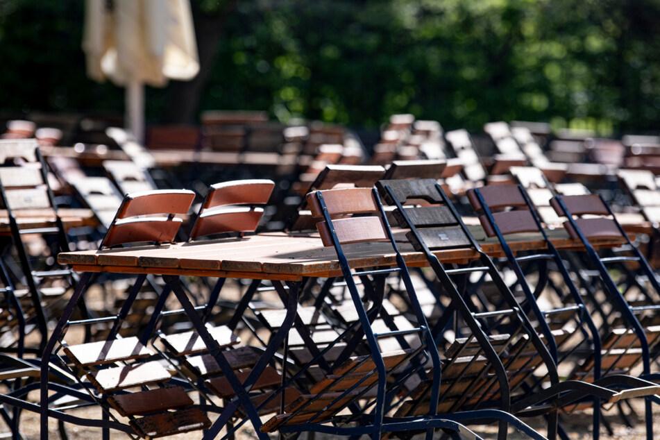 Berlin: Mehrere Stühle sind in einem geschlossenen Biergarten im Tiergarten an die Tische angelehnt.