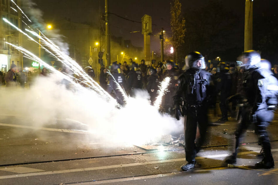 Polizeibeamte räumen eine Kreuzung und werden dabei mit Feuerwerkskörpern beschossen.