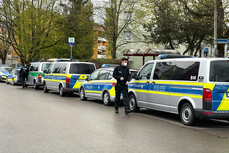 Einsatzfahrzeuge der Polizei stehen vor einem Mehrfamilienhaus, in dem eine 52-jährige Frau tot aufgefunden wurde.