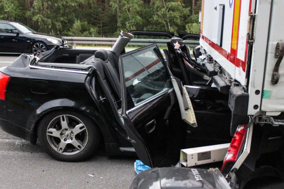 Ein Autowrack klemmt nach einem Unfall auf der Autobahn 2 (A2) unter dem Auflieger eines Lkw.