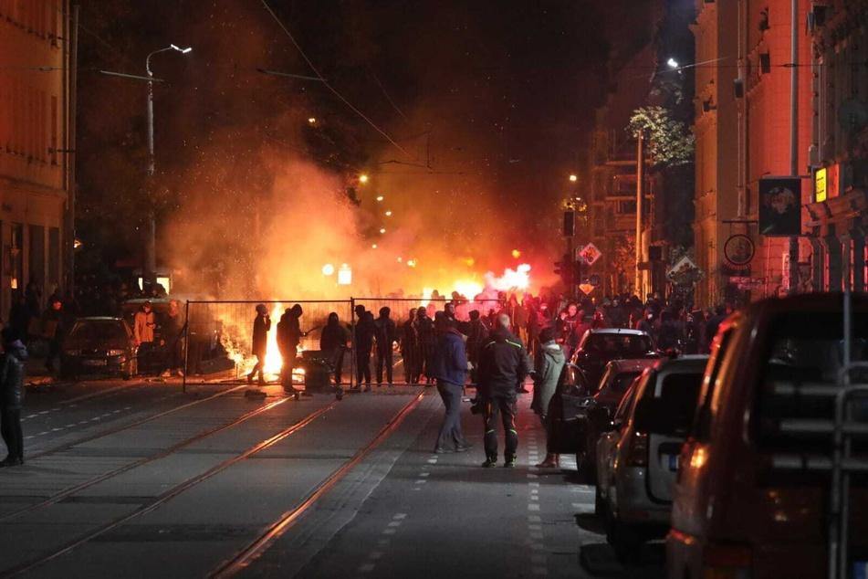 In der Wolfgang-Heinze-Straße stehen sich zündelnde Protestierende und Polizisten gegenüber.