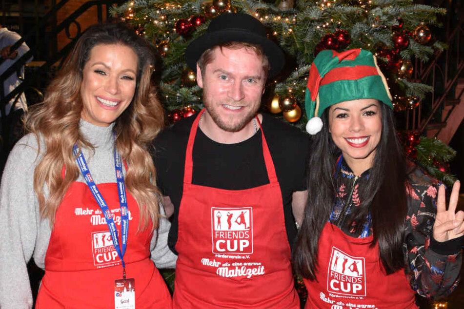 """Yasmina Filali, Schauspielerin (l.), Johannes Oerding, Sänger und Fernanda Brandao (rechts), Sängerin, lächeln in der Fischauktionshalle bei der Weihnachtsfeier """"Mehr als eine warme Mahlzeit""""."""