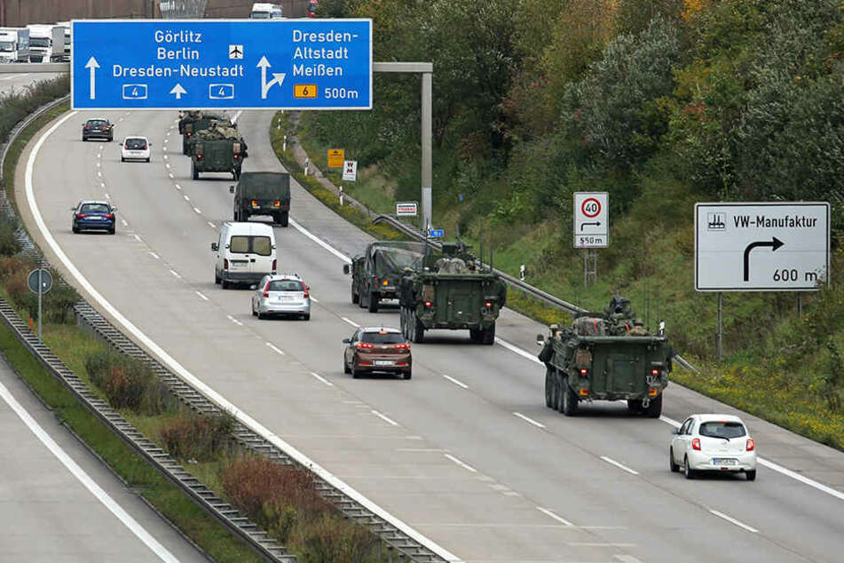 Von ungläubigen Blicken verfolgt, bewegt sich ein Konvoi der US-Army über die Autobahn.