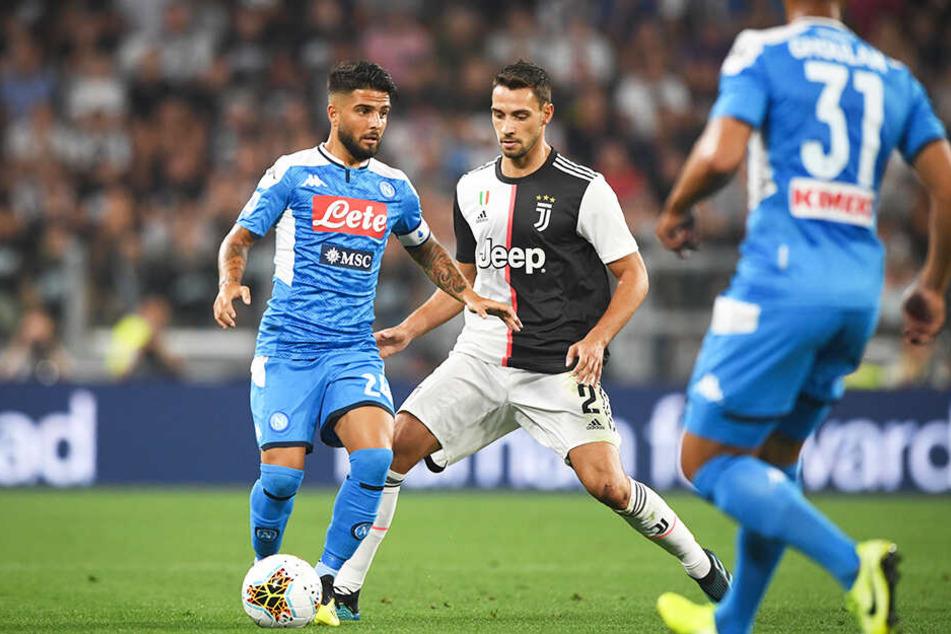 SSC-Kapitän Lorenzo Insigne (l.) behauptet den Ball gegen Juve-Verteidiger Mattia De Sciglio.