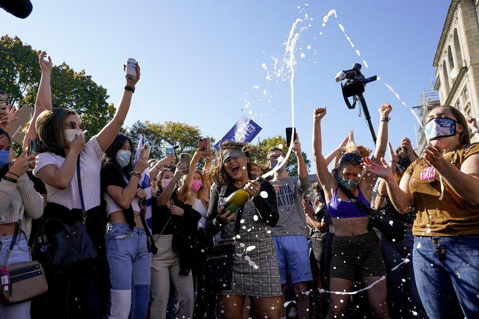 Amanda Madden versprüht Champagner, während die Menschen auf der Black Lives Matter Plaza Bidens Sieg feiern.