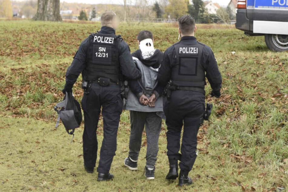 Nachdem dem Mann eine Halskrause angelegt wurde, wird er von Polizisten abgeführt.