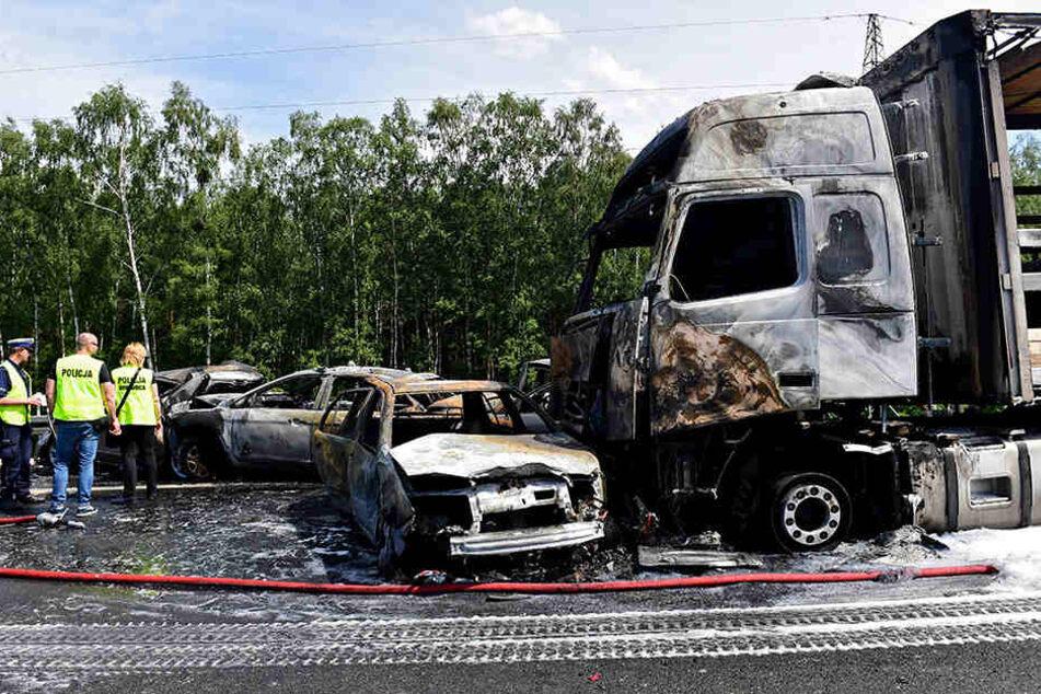 Polizisten stehen vor mehreren ausgebrannten Fahrzeugen auf der Autobahn A6 bei Stettin.