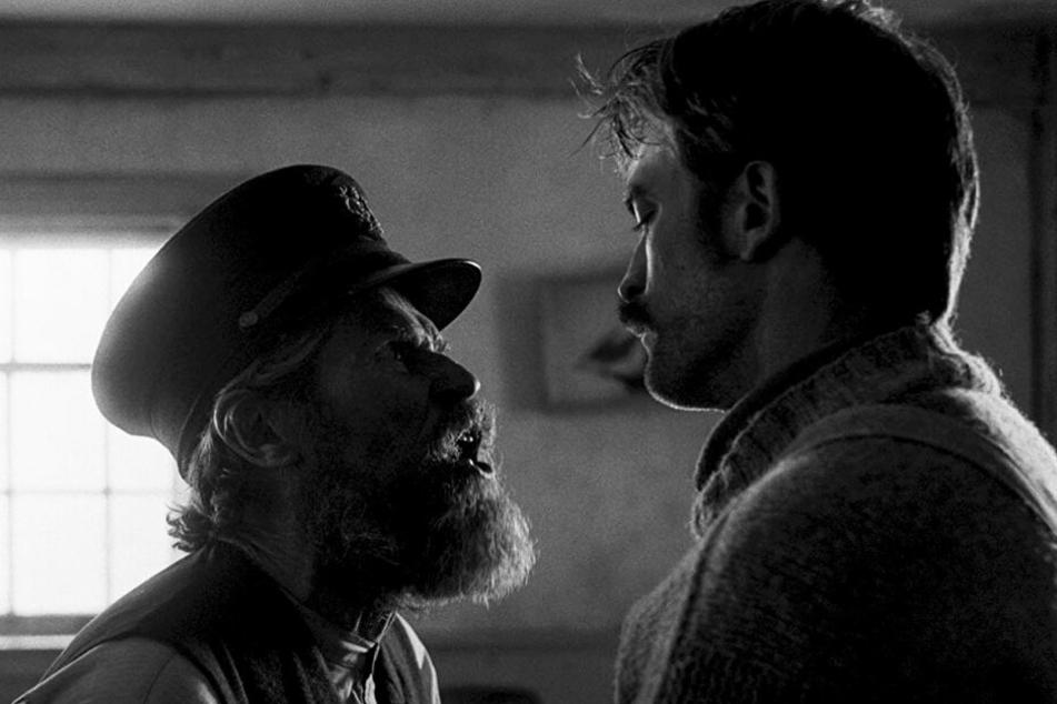 Thomas Wake (l., Willem Dafoe) übernimmt sofort die Rolle des Chefs und weist Ephraim Winslow (Robert Pattinson) unwirsch in die Schranken.
