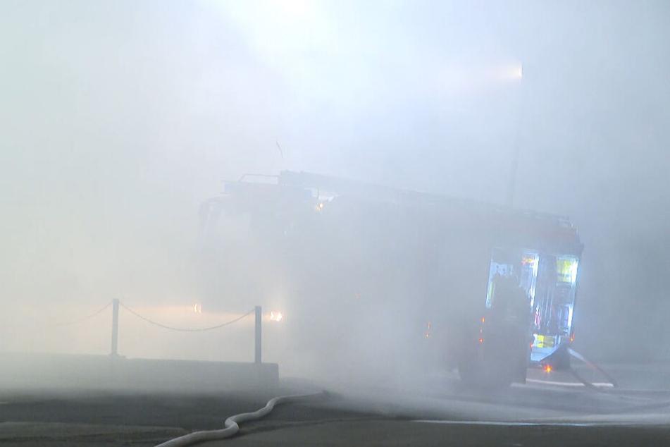 Das Feuerwehrauto ist durch die starke Rauchentwicklung kaum zu erkennen.
