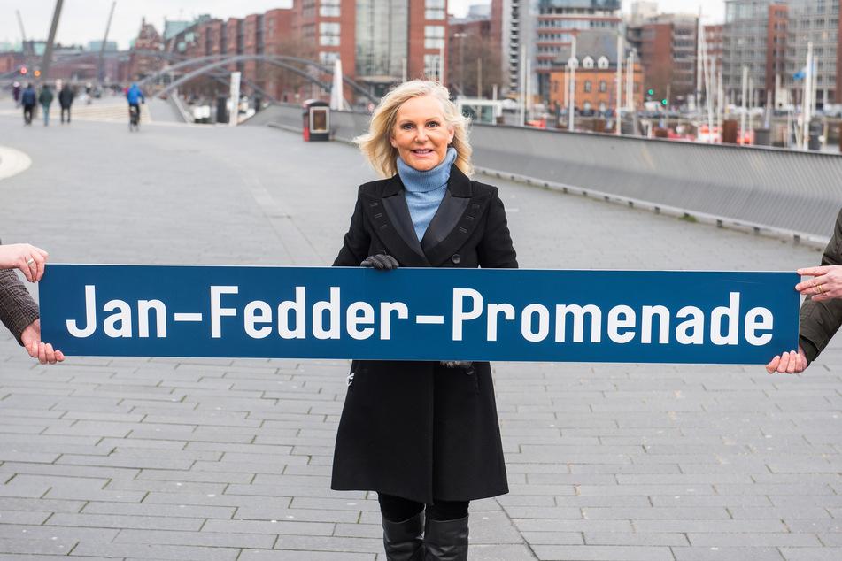 """Marion Fedder, Witwe des Schauspielers Jan Fedder (†64), steht am Hafen und hält ein Schild mit der Aufschrift """"Jan-Fedder-Promenade""""."""