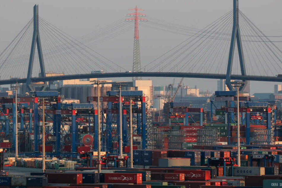 Container stehen am Containerterminal Burchardkai auf dem Gelände der HHLA, im Hintergrund ist die Köhlbrandbrücke zu sehen.