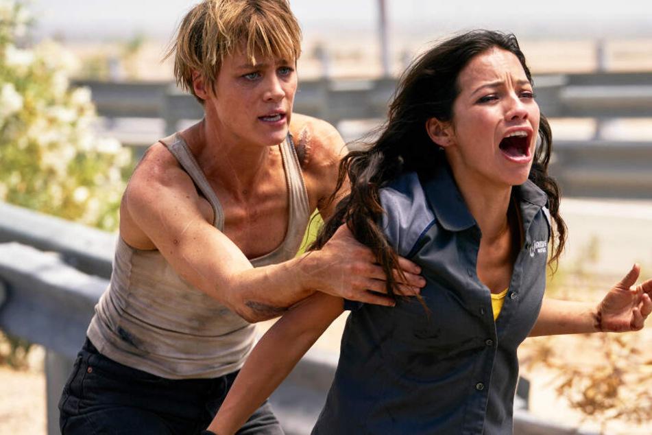 """Nur Danielle """"Dani"""" Ramos (r., Natalia Reyes) kann die Menschheit vor dem Untergang bewahren - ein Flüchtling. Deshalb wurde der """"verbesserte Mensch"""" Grace (Mackenzie Davis) aus der Zukunft durch die Zeit geschickt: Um sie zu beschützen."""