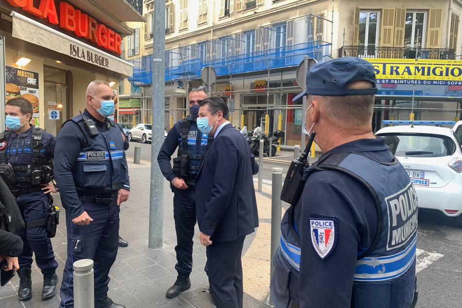 Christian Estrosi (2.v.r), Bürgermeister von Nizza, spricht mit Polizeibeamten am Ort des Messerangriffs.