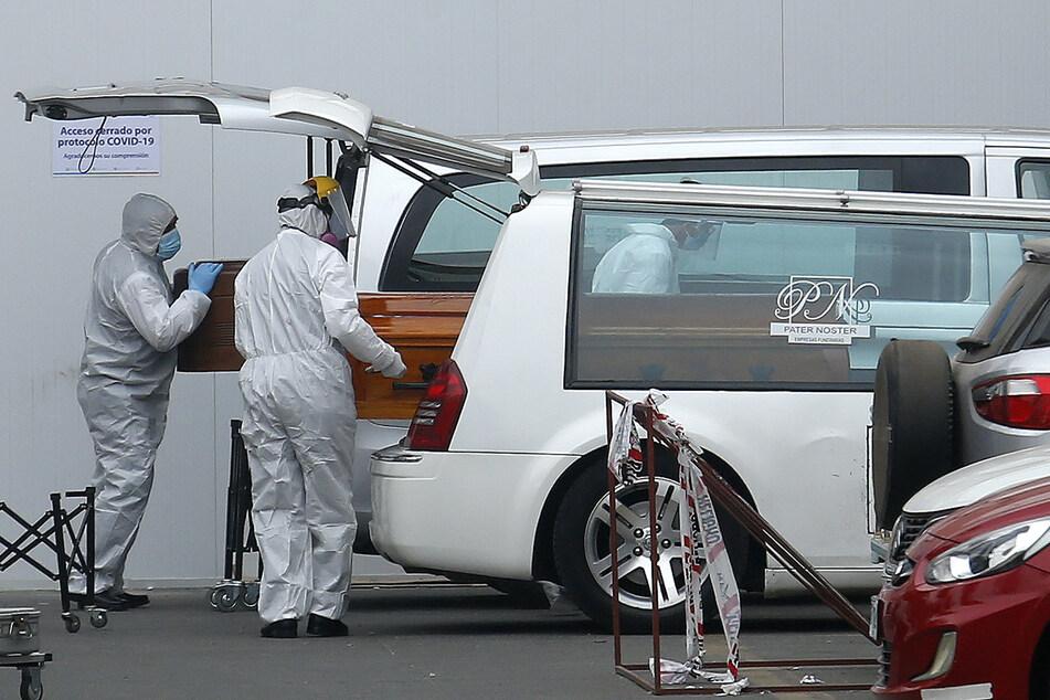 Arbeiter in Schutzanzügen legen vor einem Krankenhaus Särge in Leichenwagen.