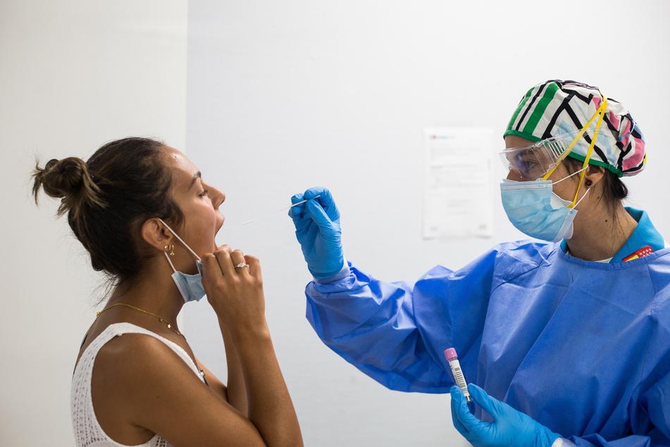 Eine medizinische Mitarbeiterin nimmt in einem Covid-19-Testzentrum in Madrid einen Abstrich bei einer Patientin.