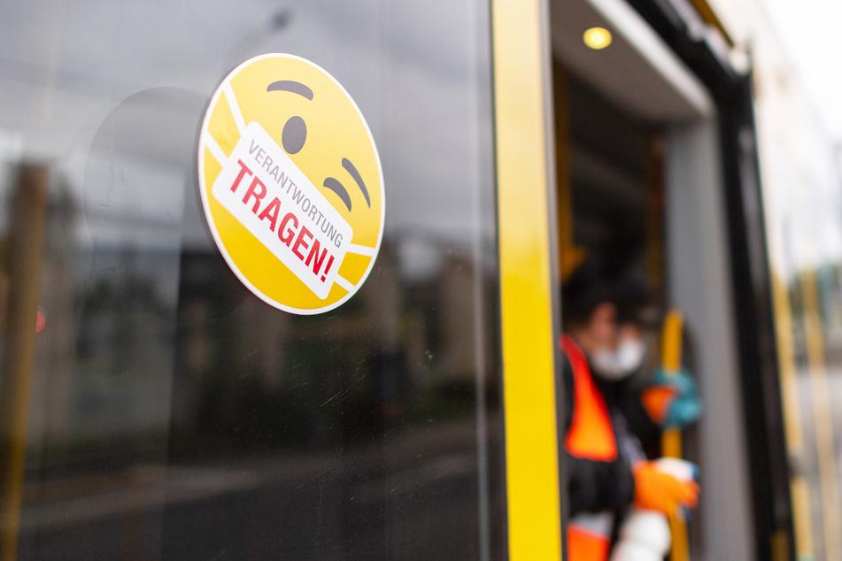 """Ein Smiley-Aufkleber mit einem Mundschutz und der Aufschrift """"Verantwortung tragen"""" klebt an der Tür einer Straßenbahn, während eine Mitarbeiterin der Dresdner Verkehrsbetriebe die Handläufe desinfiziert."""