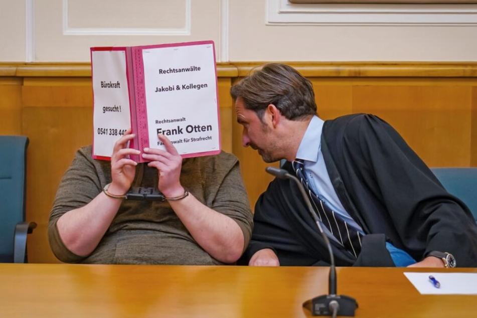 Der Rechtsanwalt Frank Otten (r) beugt sich zu dem 32-jährigen Angeklagten.
