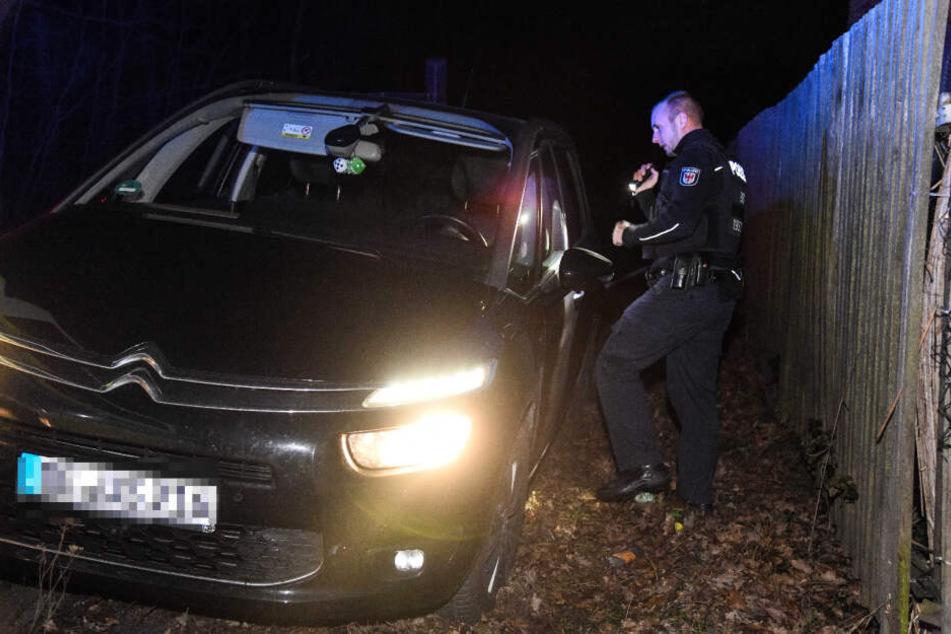 Ein Polizist untersucht den gestohlenen Wagen.