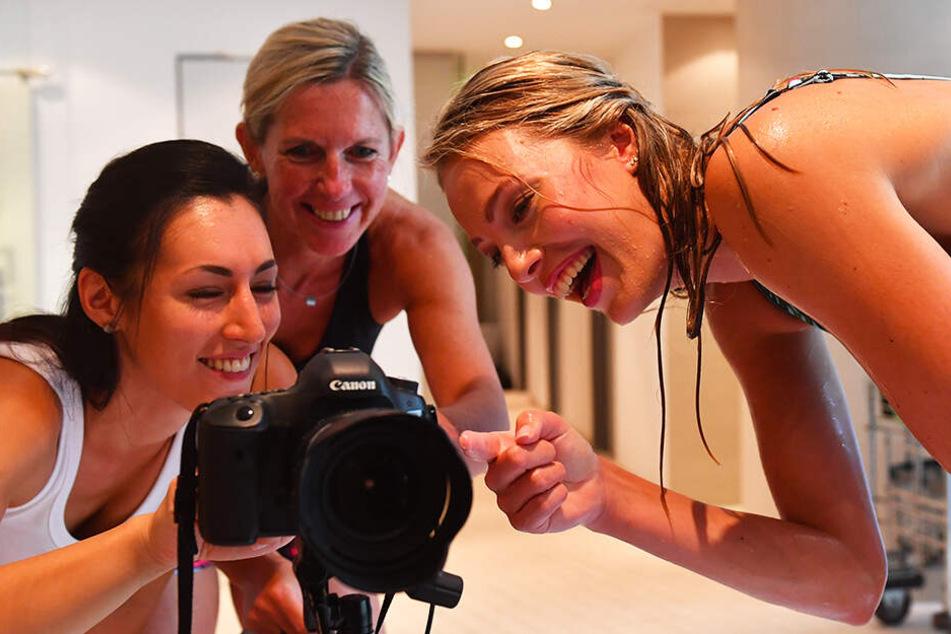 Fotografin Amelie Jehmlich, Beatrice Dömeland und Mittelblockerin Laura de Zwart (v.l.) schauen sich die gerade geschossenen Bilder an.
