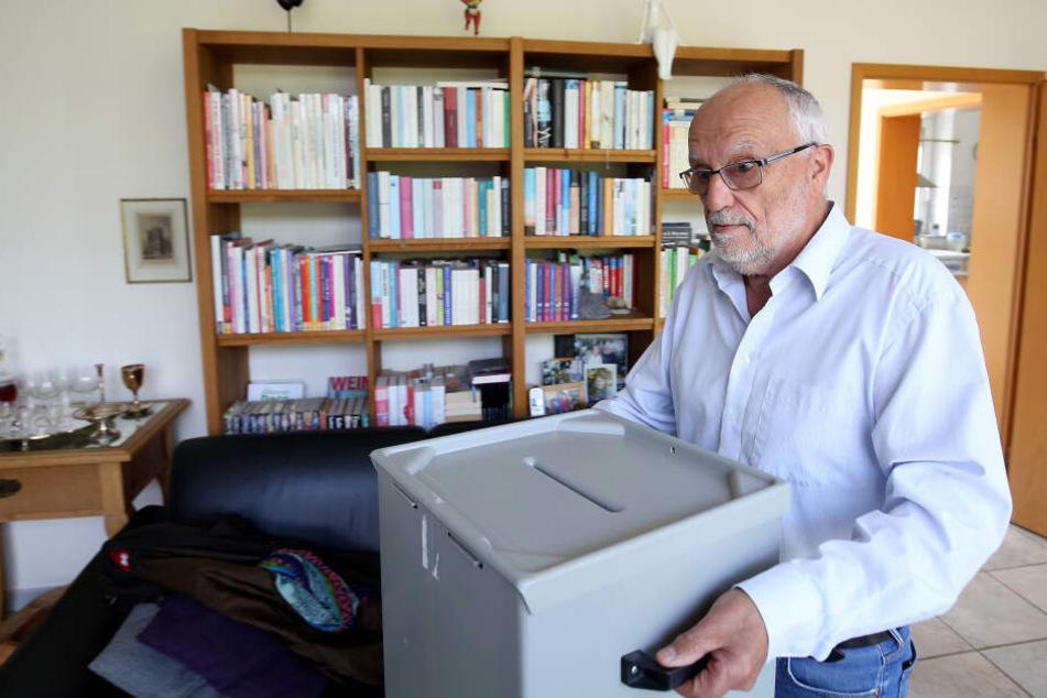 Der Rentner Johann Peter Fabrizius (69) trägt eine Wahlurne in sein Wohnzimmer.