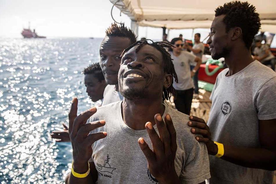 Migranten an Bord des Rettungsschiffs der spanischen Nichtregierungsorganisation Proactiva Open Arms freuen sich über ihre Ankunft in Barcelona.