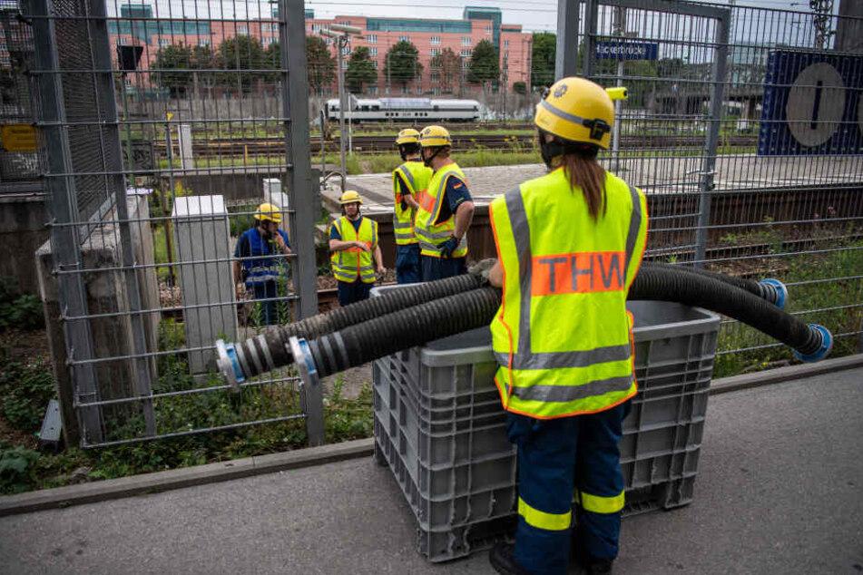 Einsatzkräfte des THW verlegen Schlauchleitungen auf den S-Bahngleisen.