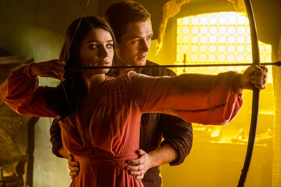 Jungfrau Marian (vorne; Eve Hewson) und Robin von Loxley (Taron Egerton) lernen sich früh kennen und lieben.