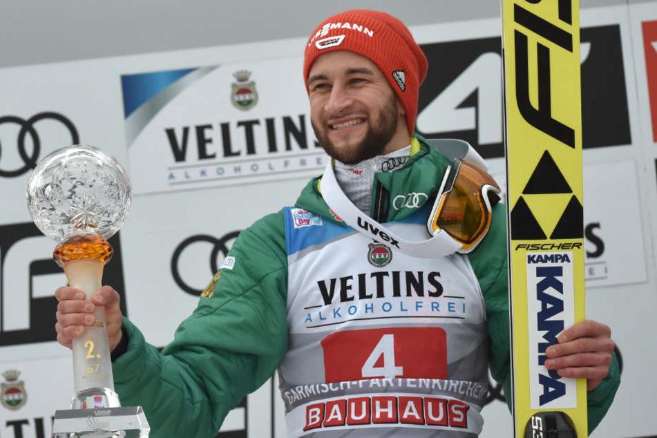 Markus Eisenbichler jubelt mit Pokal bei der Siegerehrung.