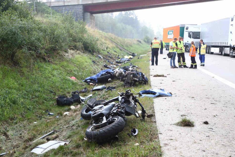 Einsatzkräfte stehen an einer Unfallstelle auf der A9, Motorräder und Trümmerteile liegen neben der Fahrbahn an der Böschung.