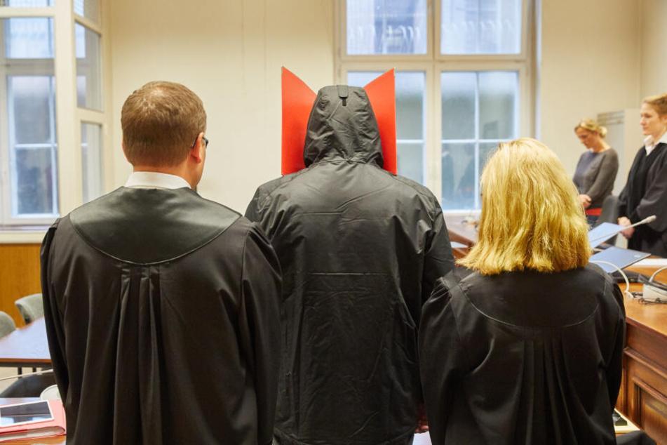 Der Angeklagte (Mitte) steht vor Prozessbeginn wegen Vergewaltigung und gefährlicher Körperverletzung im Strafjustizgebäude.