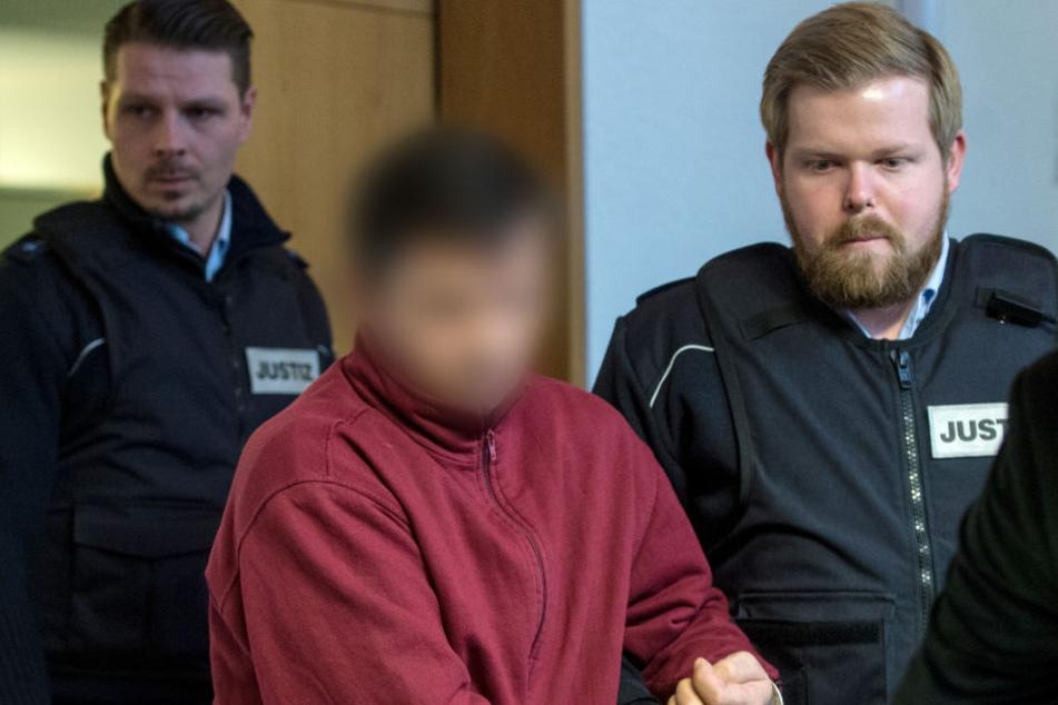Der angeklagte Lastwagenfahrer aus Rumänien wird von einem Justizmitarbeiter in den Sitzungssaal des Landgerichtes in Freiburg gebracht.